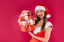 Smiling Sexy Beautiful Santa Girl Holding Gift Boxes Isolated On Burgundy