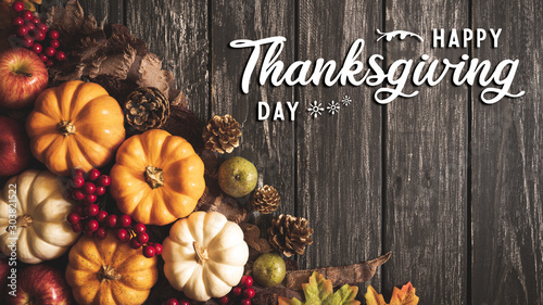 Door stickers Countryside Top view of Autumn maple leaves with Pumpkin and red berries on old wooden background. Thanksgiving day concept.