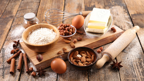 Fototapeta baking food ingredient on wooden board, flour-egg-nut-butter and spices
