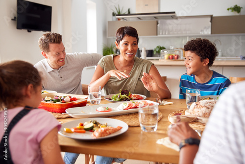 Fototapeta Multi-Generation Mixed Race Family Eating Meal Around Table At Home Together obraz