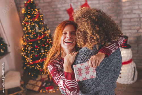 Obraz Couple having fun while exchanging Christmas presents - fototapety do salonu