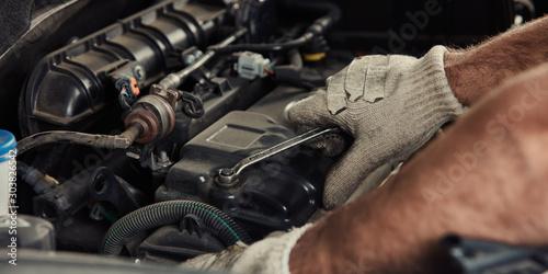 Hand am Motor beim Auto reparieren in Werkstatt