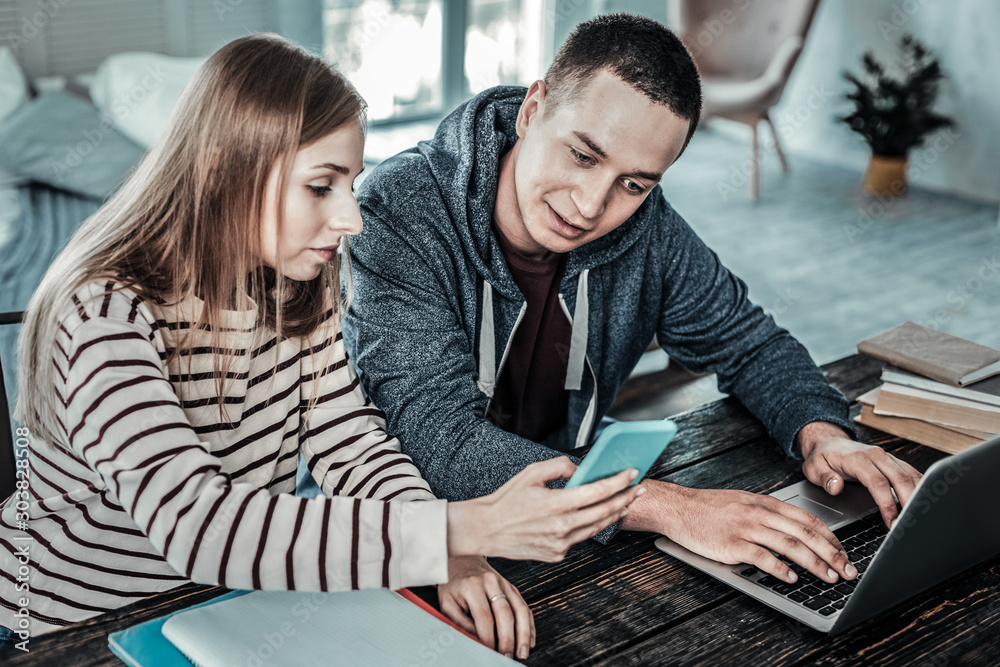 Fototapety, obrazy: Nice positive man looking at her girlfriends smartphone