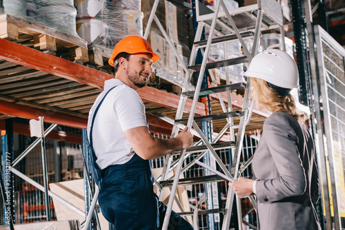 Obraz smiling warehouse worker standing on ladder and looking at businesswoman in helmet - fototapety do salonu