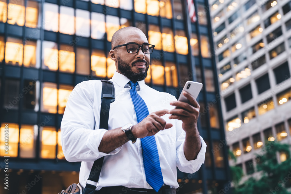 Fototapeta Ethnic bearded executive using smartphone