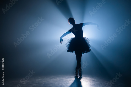 Ballerina in black tutu dress dancing on stage with magic blue light and smoke Canvas Print