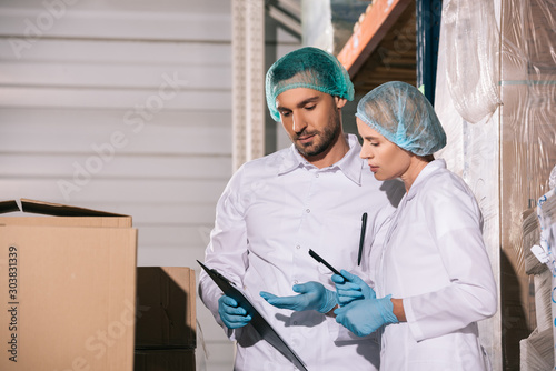 two storekeepers in white coats and hairnets looking at clipboard in warehouse Canvas Print
