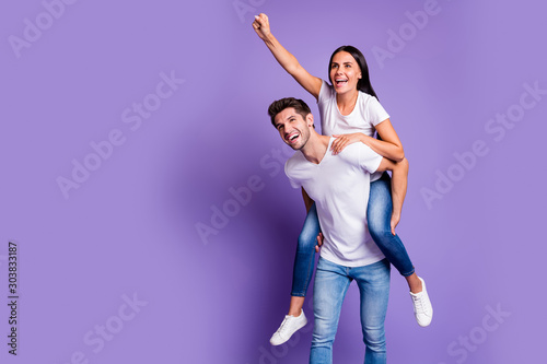 Photo of piggyback pretty cute couple in jeans denim white t-shirt with man carrying girl her directing him forward smiling toothily isolated pastel color background violet
