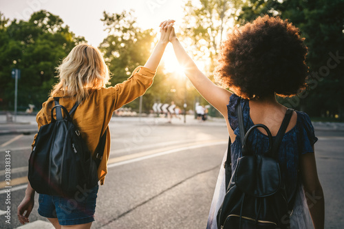 Couple of young women from the back, holding hands with arms raised and they walk in the street at sunset - Two millennials are happy - 303838334