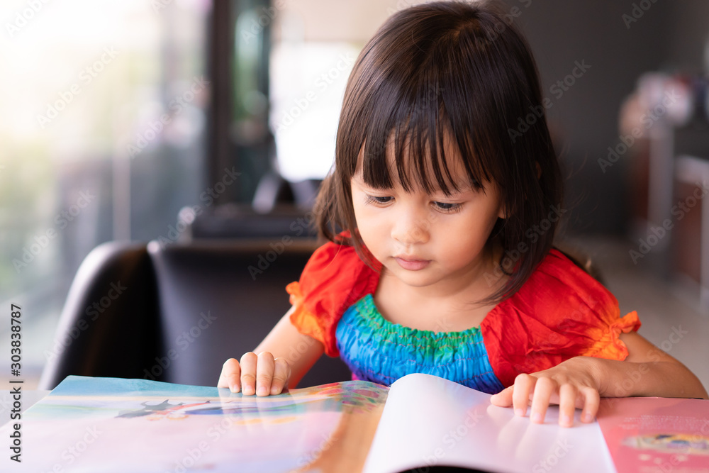 Fototapeta Adorable asian little girl is sitting and reading storybook on the sofa with concentrate happy moment, concept of activity for kid education.