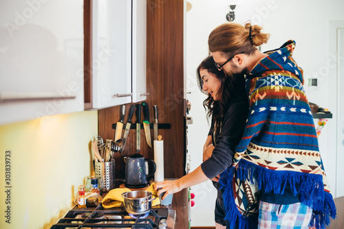 Affectionate young couple cooking food in kitchen at home Wallpaper Mural