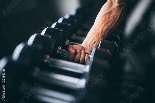 Obraz Rows of dumbbells in the gym with hand - fototapety do salonu