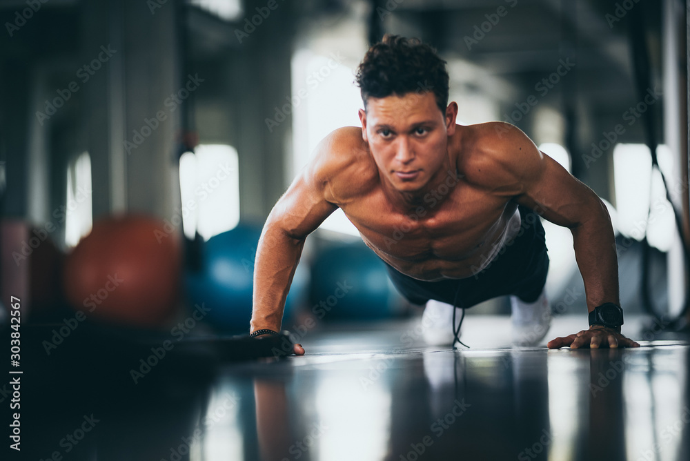 Fototapeta Sport. Young athletic man doing push-ups. Muscular and strong guy exercising.