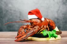 Fresh Red Lobster With Christmas Hat Shellfish Cooked In The Seafood Restaurant - Steamed Lobster Dinner Food On Wooden Christmas Table Setting Celebrate In Holiday Winter Festive