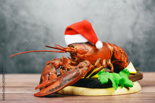 Fresh red lobster with christmas hat shellfish cooked in the seafood restaurant - Steamed lobster dinner food on wooden christmas table setting celebrate in holiday winter festive - 303842999