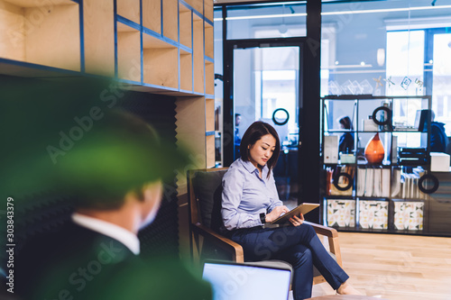 Photo Asian woman with tablet sitting in office lounge