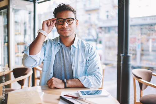 Valokuvatapetti Half length portrait of mature handsome hindu entrepreneur dressed in stylish jeans clothes correcting glasses while sitting at table