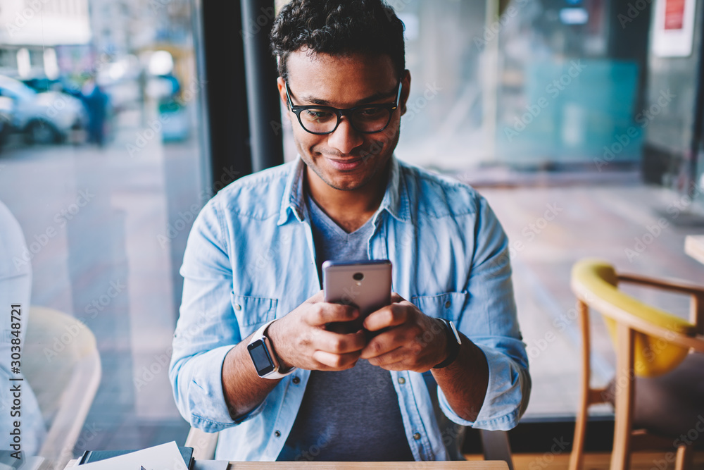 Fototapeta Cropped image of positive male person in glasses for better vision chatting with friends in social networks on smartphone.Mature happy man sending funny messages using application on cellular