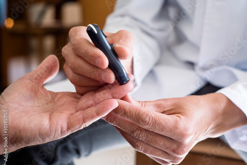 measuring the blood glucose level of an old man Canvas Print