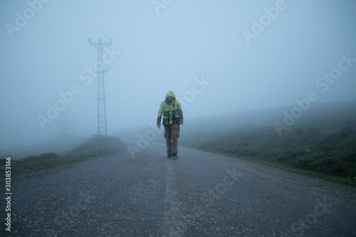 Fotomural  man coming back from the unknown in a foggy road with a yellow jacket