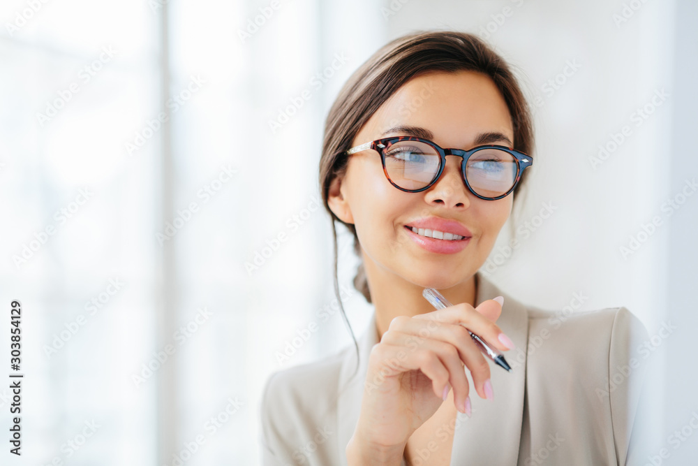 Fototapeta Smiling prosperous lady work in business sphere, holds pen, wears elegant clothes, has healthy skin, minimal makeup, looks somewhere, poses indoor against blurred white background, copy space left
