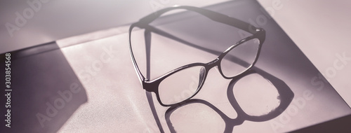 Obraz Glasses placed on the laptop in the library. - fototapety do salonu