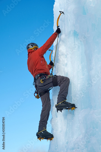 Photo Alpinist man with ice tools axe climbing a large wall of ice