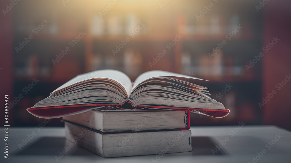 Fototapety, obrazy: Stack of books in the library and blur bookshelf background