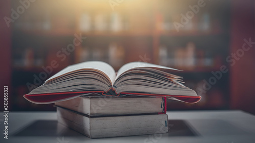Obraz Stack of books in the library and blur bookshelf background - fototapety do salonu