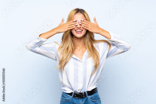 Young blonde woman over isolated blue background covering eyes by hands