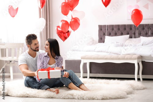 Fototapeta Young man presenting gift to his girlfriend in bedroom decorated with heart shaped balloons. Valentine's day celebration obraz