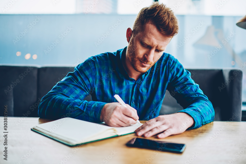 Fototapeta Skilled red haired student writing down homework in copybook studying at wooden table in coworking space.Pensive young man dressed in casual shirt noting checklist in notepad during free time