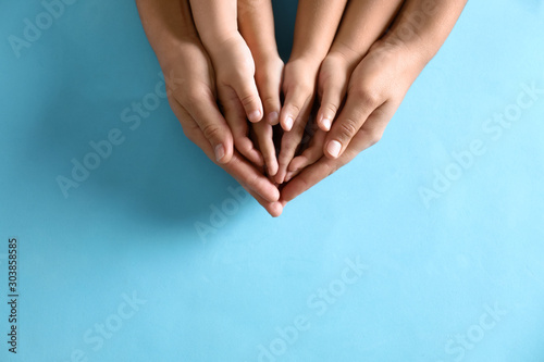 Obraz Mother holding hands with her children on blue background, top view. Happy family - fototapety do salonu