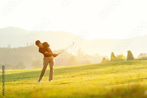Fotomural  Professional Golfer asian man swing and hitting golf ball practice at golf driving range and fairway in sunny morning day on multiethnic club golf