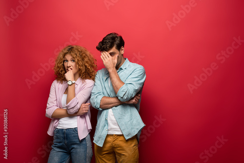 Fotografía young skeptical couple in casual clothes isolated on red