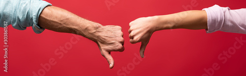 Obraz partial view of couple showing thumbs down, isolated on red - fototapety do salonu