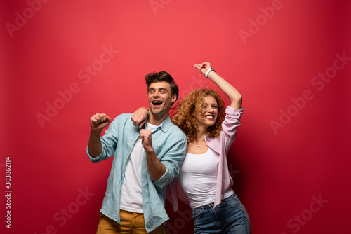 beautiful excited couple dancing in casual clothes isolated on red