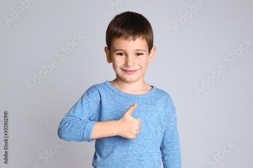 Fotografiet Portrait of happy little boy on light grey background