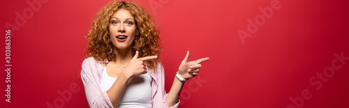 attractive surprised redhead woman pointing isolated on red Canvas-taulu