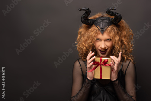 Obraz na plátně sexy woman in maleficent costume holding gift box for halloween on black