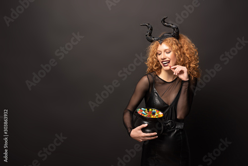 Fotografie, Tablou  beautiful curly woman in maleficent costume holding pot with sweets for hallowee