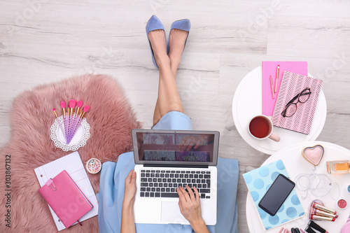 Fotografia Beauty blogger with laptop and cosmetics sitting on floor, top view