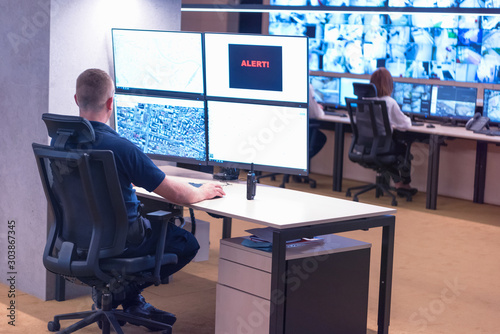 Security guard monitoring modern CCTV cameras in surveillance room Tableau sur Toile