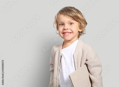Very cute little boy with a book in his cardigan - 303868373