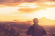 Copy space of backpack man looking view on top of mountain and sunset sky abstract background.