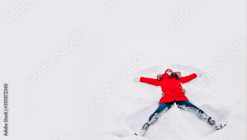 Foto Happy young woman in red lying on snow and making snow angel figure with hands a