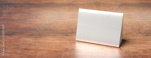 Fotografija  Table tent, reserved card sign empty blank on a wooden table, 3d illustration