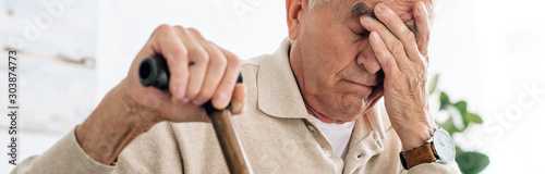 Fototapeta panoramic shot of senior man having headache and holding wooden cane in apartment obraz