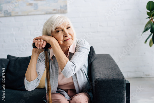 smiling senior woman with wooden cane looking at camera in apartment Fototapet