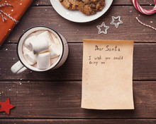 Wish List Letter To Santa Claus From Child On Wooden Background